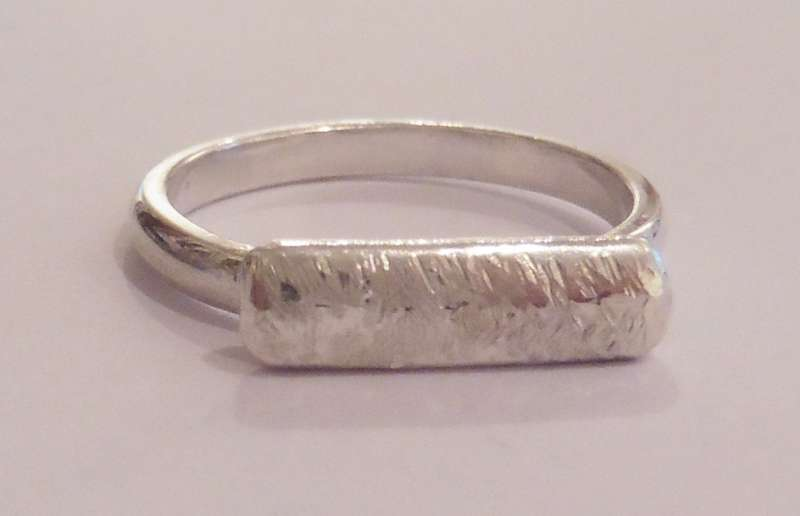 Silver ring with textured bar